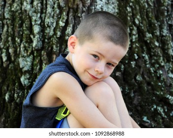 Little boy sits besides a tree outdoors.  He leans his head against his knees as he enjoys being outside.