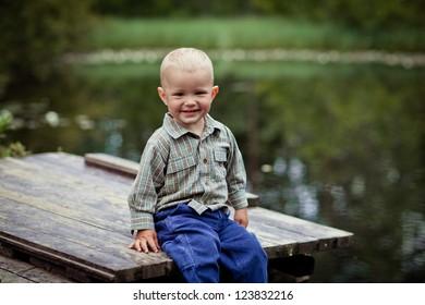 Little boy sits on a bridge by the pond
