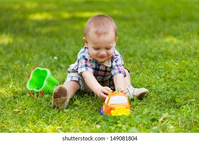 little boy sits on a grass and plays toys
