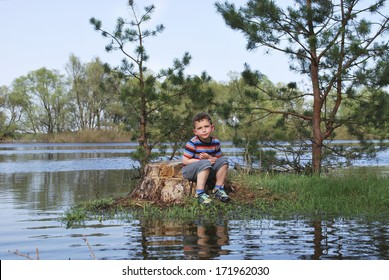 Little boy sits on the stump near the river shores published Moh.