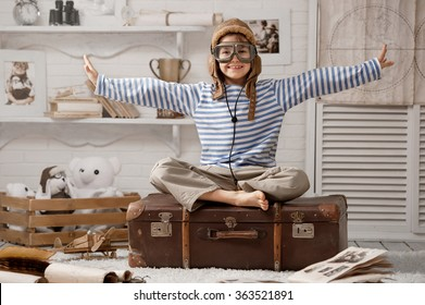 Little boy sits on a suitcase playing with model airplane