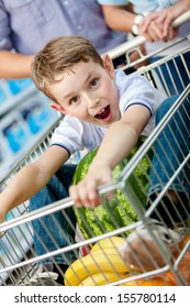 Little boy sits in the shopping trolley with watermelon and other products bought by parents