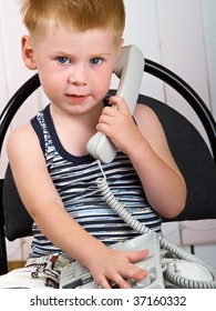 The little boy sits with a telephone tube in hands