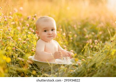 little boy sitting in a basin on the nature and bathed in summer