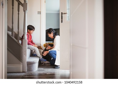 Little boy is sitting at the bottom of the stairs in his home to put his shoes on with help from his grandmother.