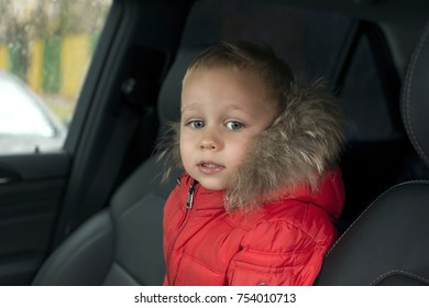little boy is sitting in the car autum in the jacket