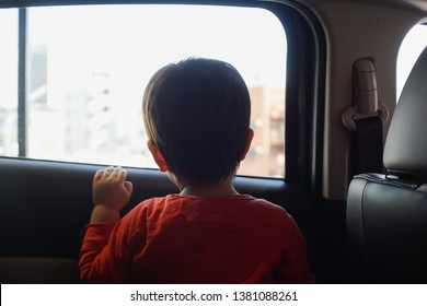 Little boy sitting in the car and look out from the car window.