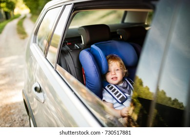Little boy sitting in the car seat in the car.