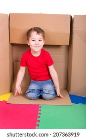little boy sitting in a cardboard box and laughing into the camera