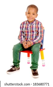little boy sitting in chair isolated in white