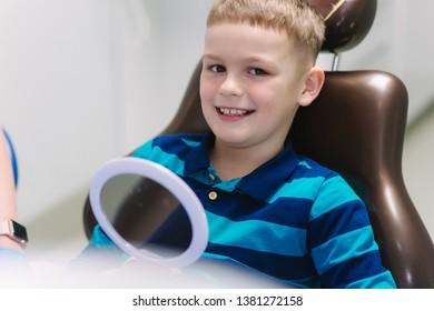 Little boy sitting in dantist chair with mirror. Male patient look at his teeth