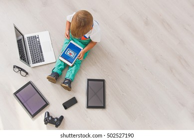 Little boy sitting with digital gadgets in studio