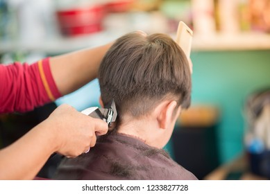 Little boy sitting for hair cut at barber shop