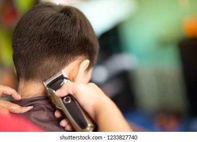 Little boy sitting for hair cut at barber shop