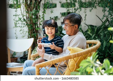 Little boy sitting with his grandpa on wicker chair in backyard and play the game on smartphone, wearing wireless headphone.