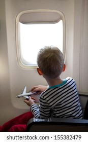 little boy sitting inside the plane and playing with his toy plane