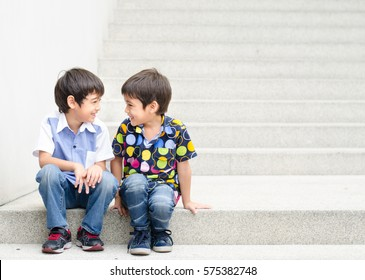 Little boy sitting look to each other on step