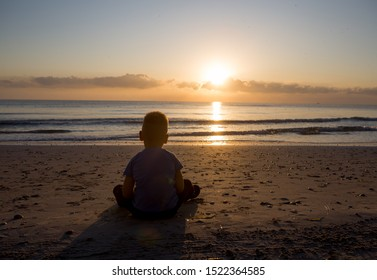 little boy  sitting  and looking at the dawn on the sunrise back
