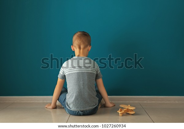 Little boy sitting near dark wall in empty room. Autism concept