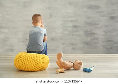 Little boy sitting near wall in empty room. Autism concept