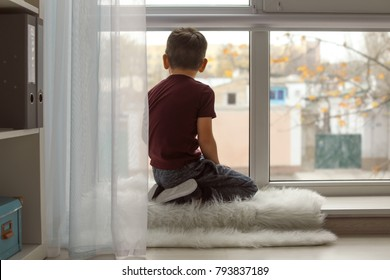 Little boy sitting near window at home. Child autism