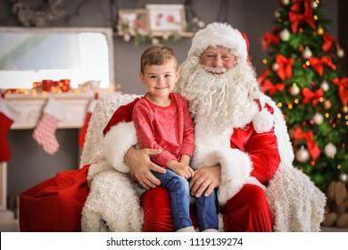 Little boy sitting on authentic Santa Claus' lap indoors