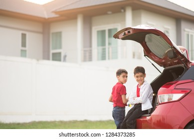 Little boy sitting on the back door of the car with ahnd wave