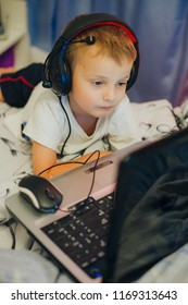 little boy sitting on a bed wearing headphones and looking at a laptop