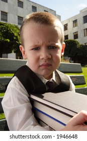 Little boy sitting on a bench holding a stack of books with a disgusted look on his face. Collegiate setting.