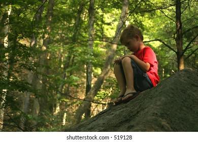 A little boy sitting on a big rock pouting.