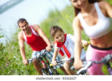 A little boy sitting on bike between mother and father