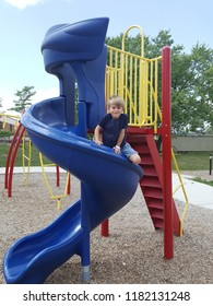 Little boy sitting on the edge of a bright blue spiral slide at a playground.
