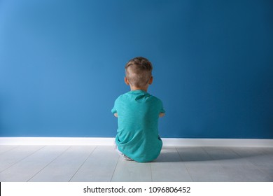 Little boy sitting on floor near color wall in empty room. Autism concept