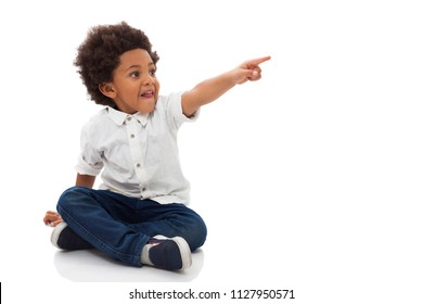 Little boy sitting on the floor pointing something at side