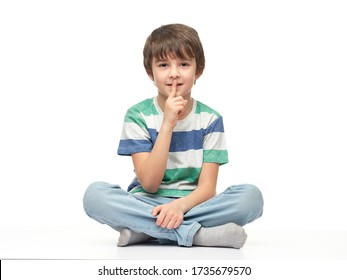 Little boy is sitting on the floor and putting a finger on his lips. Separate on a white background.