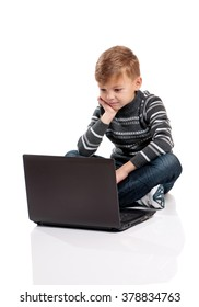 Little boy sitting on floor with laptop on white background