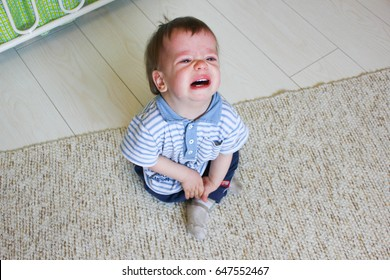 Little boy sitting on the floor, he's upset and crying. The child is crying sitting on the floor in the room.