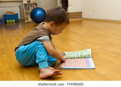 Little boy is sitting on the floor with a book