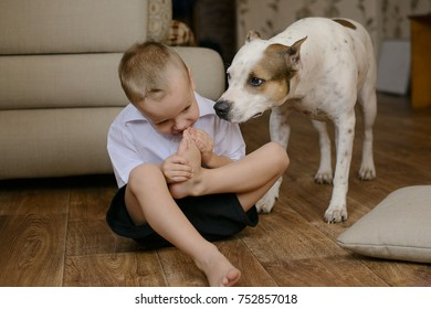little boy sitting on the floor and biting his toes and the dog stares