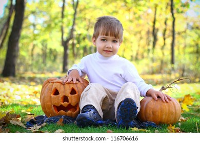 Little boy sitting on the grass in the forest with two halloween pumpkins