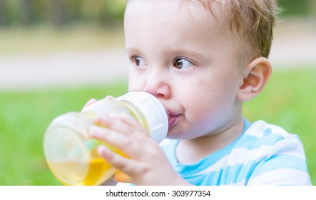 Little boy sitting on grass and drinking his beverage at the end of the funny hot summer day