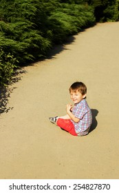 Little boy is sitting on a ground and laughing
