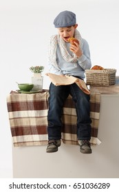 Little boy sitting on kitchen counter having breakfast, reading newspaper, acting as old.