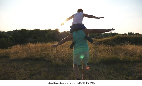 Little boy sitting on the shoulders of his father and playing raised hands as airplane outdoor. Dad carrying son and raised arms as plane at meadow. Family spending time together at nature. Rear view