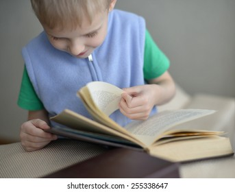 Little boy sitting on sofa with book at home