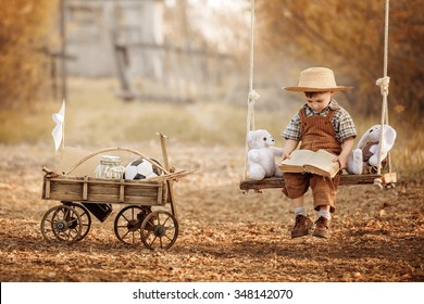Little boy sitting on a swing and reading a book his toys