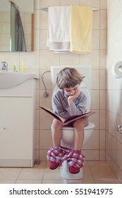Little boy sitting on toilet reading book