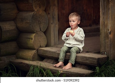 Little boy sitting on the wooden porch and eating apple in the country in Russia. Image with selective focus and toning