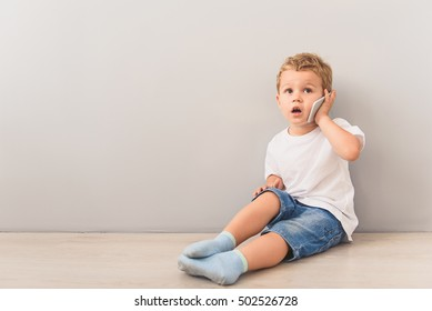 Little boy sitting with smartphone in studio