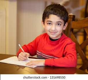 Little Boy Sitting at a Table and Doing His Homework
